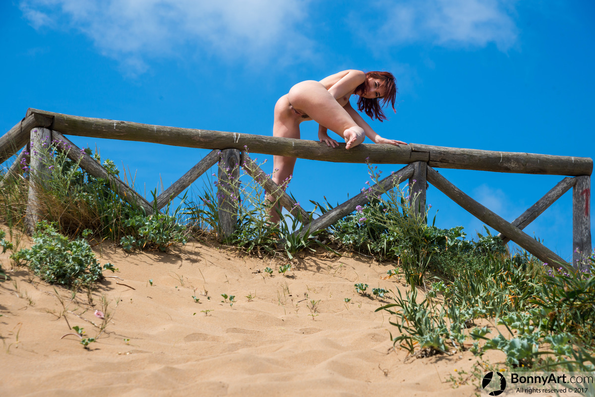 Nudist Woman Jumping the Fence on the Beach
